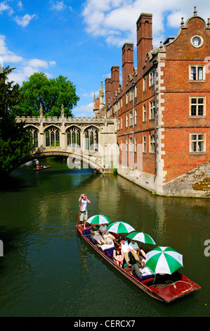 Tourists enjoying a trip along the River Cam by the Bridge of Sighs in a punt at St Johns College. - Stock Photo