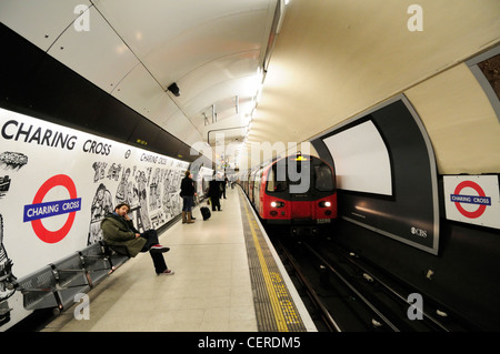 A tube train arriving alongside a platform of the Northern line at Charing Cross Underground Station. - Stock Photo