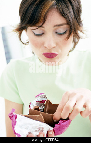 Female standing in living room holding up a half unwrapped foil wrapped chocolate Easter egg broken into pieces - Stock Photo