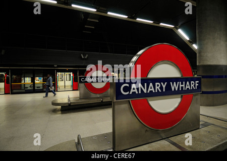 A tube train waiting at a platform in Canary Wharf Underground Station. - Stock Photo