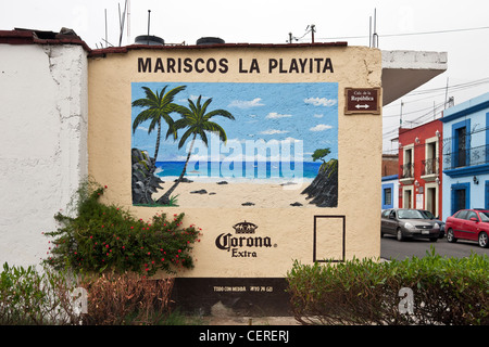beautifully colored advertising mural of idyllic tropical beach hand painted on outside wall of seafood restaurant - Stock Photo