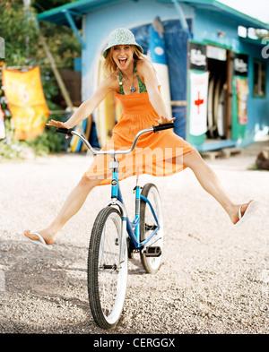 Female blonde hair wearing green swimsuit and orange strapless dress blue hat free wheeling on pushbike looking - Stock Photo