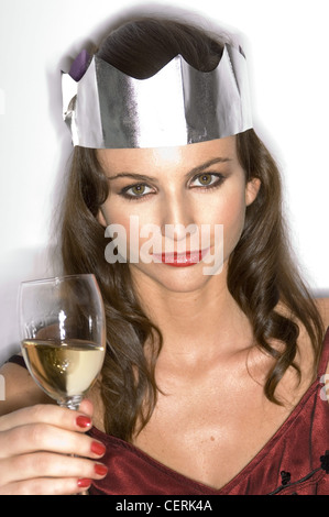 Female with brunette hair wearing dark red satin dress, silver paper hat, smokey brown eye make up Holding glass - Stock Photo
