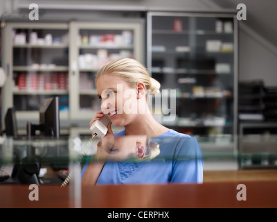 Young woman at work as receptionist and nurse in hospital and talking on the phone - Stock Photo