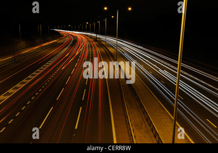 Night view from a bridge of light trails from traffic on the M25 motorway.