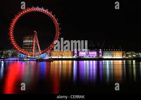 The London Eye and County Hall bathed in colourful lights on the South Bank. - Stock Photo