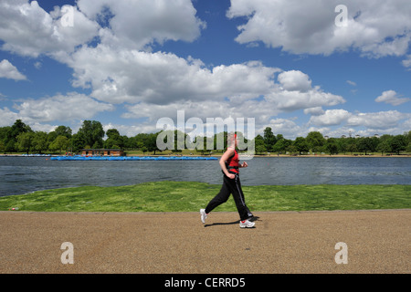 A woman jogging past the Serpentine in Hyde Park. - Stock Photo