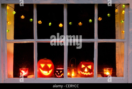 Carved Halloween pumpkins, a lantern and candles in orange and red glasses on a window sill Halloween fairy lights - Stock Photo