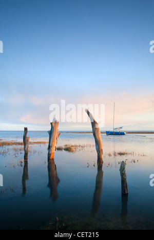 Thornham Harbour and the remains of an ancient wooden pier at high tide on the North Norfolk Coast. - Stock Photo