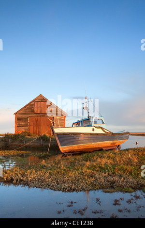 A boat moored by the old coal shed at first light at Thornham Harbour on the North Norfolk Coast. - Stock Photo
