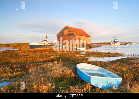 Boats and the old coal shed at first light at Thornham Harbour during a high tide on the North Norfolk Coast. - Stock Photo