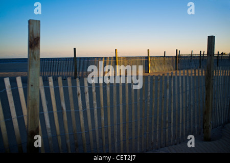 A windbreak fence on the beach at sunset in Ocean City Maryland, USA - Stock Photo