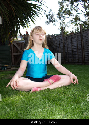 Female child blonde shoulder length hair, wearing a blue t shirt and black shorts, sitting in lotus yoga position - Stock Photo