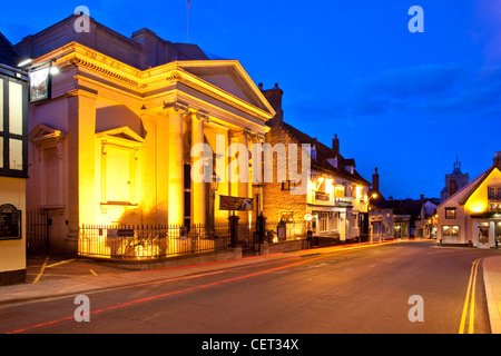 A light trail from a car passing Diss Corn Hall, an arts centre and venue in the town centre at dusk. - Stock Photo