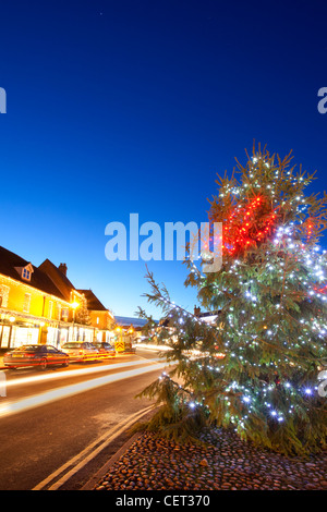 Light trails from traffic passing a Christmas tree with decorations by the side of the road in the Georgian market - Stock Photo