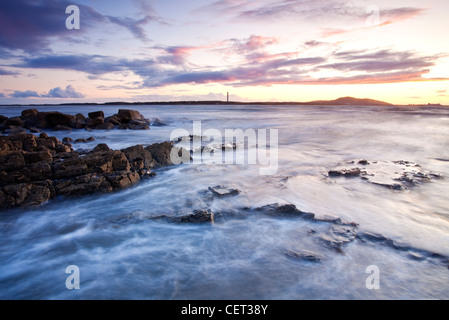 Sunset looking towards Holyhead Mountain viewed from Porth Penrhyn-Mawr on the Isle of Anglesey. - Stock Photo