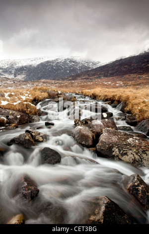 Water flowing down from mountains over rocks in the Snowdonia National Park in Winter. - Stock Photo