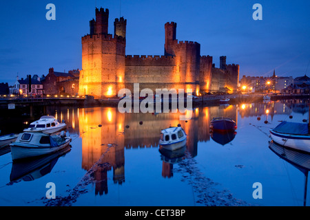 Caernarfon Castle at the mouth of the Seiont river at dusk. - Stock Photo