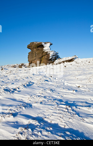 Snow on and surrounding Mother Cap, a large gritstone rock formation in the Peak District National Park. - Stock Photo