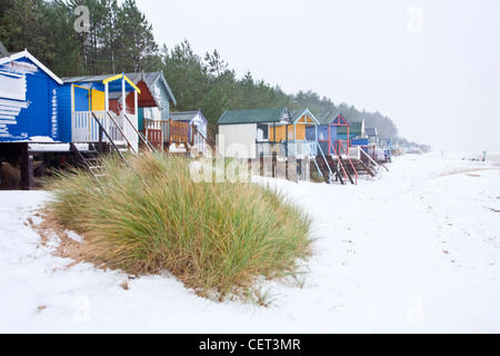 The famous colourful beach huts at Wells-next-the-Sea following winter snowfall on the Norfolk Coast. - Stock Photo
