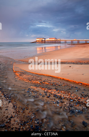 Stormy light over Cromer Pier shortly before sunset on the North Norfolk Coast. - Stock Photo
