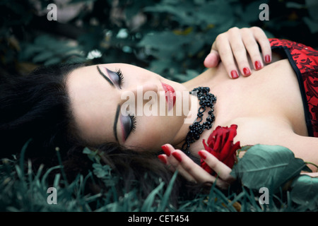 Young woman with dark hair wearing red dress lying on her back outdoors holding a single rose with her eyes closed - Stock Photo