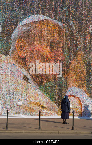 a nun looking at a huge collage of Pope John Paul II, Krakow (Cracow), Poland - Stock Photo