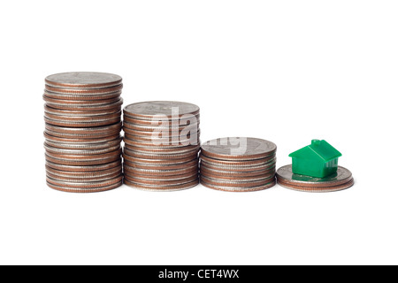 Toys house and pile of coins representing downgrade to a smaller home - Stock Photo