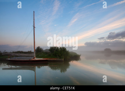 A sailing boat in dawn mist on the River Thurne in the Norfolk Broads. - Stock Photo