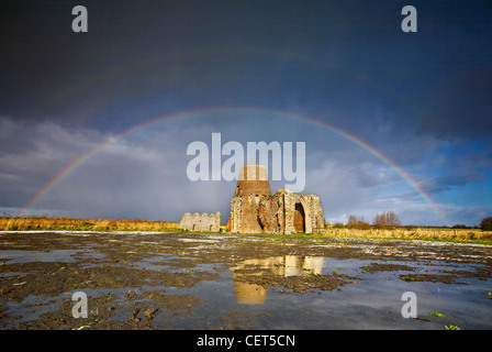 A rainbow arched over the windmill and gatehouse of St Benets Abbey (the abbey in the marshes) on the Norfolk Broads. - Stock Photo