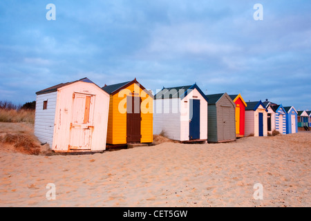 A row of colourful beach huts on the sandy beach at Southwold on the Suffolk Coast at dawn. - Stock Photo