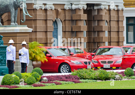 Red BMW Thai State coaches in front of Grand Palace, Bangkok, Thailand guarded by two Royal Guards and Elephant - Stock Photo