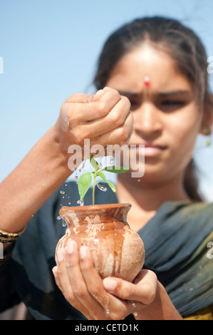 Indian teenage girl sprinkling water over a plant seedling in a clay pot. India - Stock Photo
