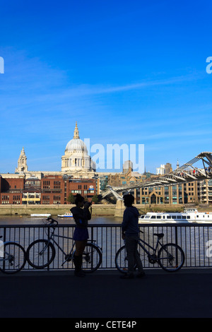 A young couple take photos across the river Thames in front of St.Paul's Cathedral in London, UK. - Stock Photo