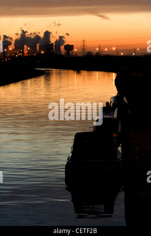 A view across water to smoke rising from industrial chimneys at sunset in Pontefract. - Stock Photo