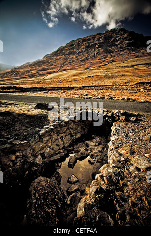 Rocky outcrops and mountains beside a road in the The Lake District. - Stock Photo