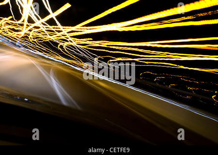 A view from a moving car to light trails on the M1 motorway at night.