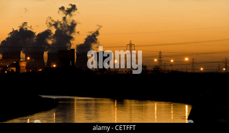 A dusk view across the river to smoke rising from industrial chimneys in Pontefract. - Stock Photo