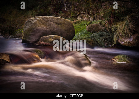 Fast running water cascading over rocks in a stream in the Lake District. - Stock Photo
