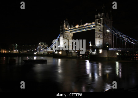 A view over the Thames to an illuminated Tower Bridge at night. - Stock Photo