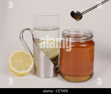 Silver mug steamed glass containing hot water and a lemon slice silver spoon hanging over opened jar of honey half - Stock Photo