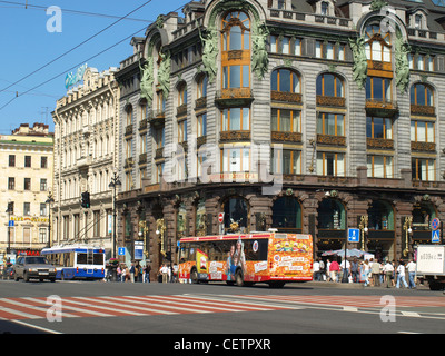 Tourist buses on a street in St. Petersburg Russia on a sunny day with tram wires overhead and an empty zebra crossing. - Stock Photo