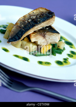 Grilled Mackerel Warm Potato Salad: Two mackerel fish fillets on diced potatoes and green beans, drizzled olive - Stock Photo