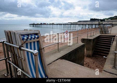 Deck Chairs on the Promenade at Teignmouth with the Grand Pier in the background, Devon, England. - Stock Photo