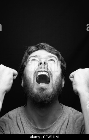 Scream of angry rebel man over black - Stock Photo
