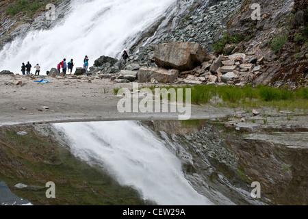 Tourists contemplating the Nugget Falls. Mendenhall glacier. Juneau. Alaska. USA - Stock Photo
