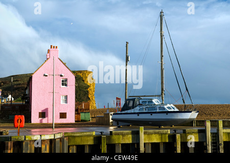 Colourful scene of house, cliffs and boat taken at West Bay harbour near Bridport, Dorset, uk after a storm in winter - Stock Photo