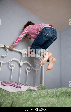 Seven year old girl holding bed frame and jumping high off her bed. - Stock Photo