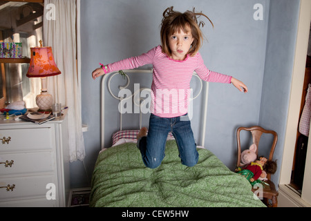 Six year old girl jumping on her bed. - Stock Photo