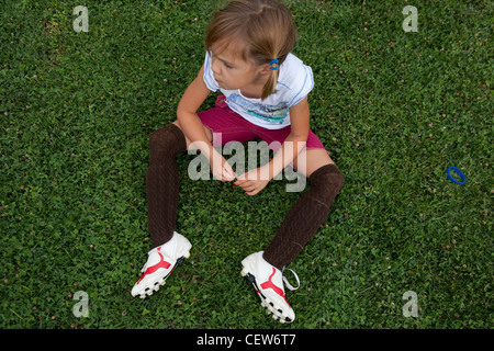 Six year old girl sitting in grass wearing soccer cleat and shin guards. - Stock Photo